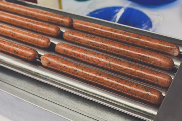 Sausages on professional machine for hot dog preparation