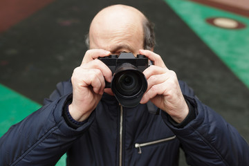 An elderly man with a mirrorless camera chooses a frame on the street