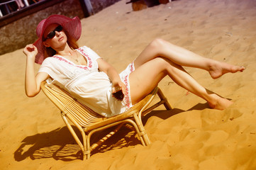 Blonde in a chaise longue on the beach wearing a hat with a glass of wine