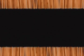 Frame of color pencils on black background