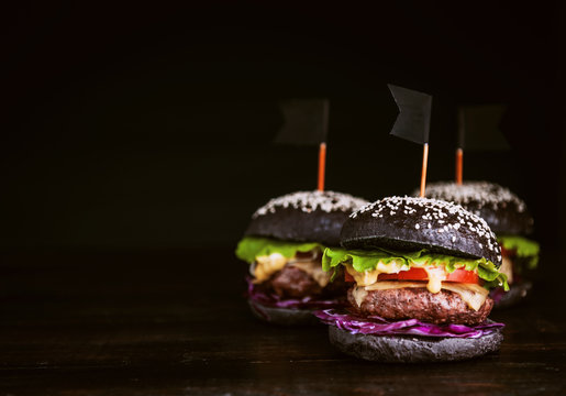 Delicious and juicy black burger with a large cutlet of meat on a black background