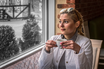 A girl drinks coffee in a restaurant and looks thoughtfully out the window