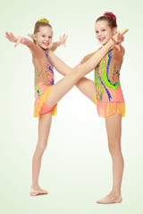 Two girls gymnast sitting on splits.