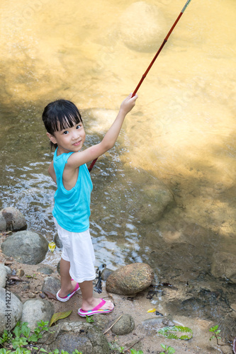 Happy asian chinese little girl angling with fishing rod for Little girl fishing pole