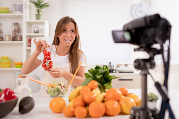 Beautiful young woman filming her blog broadcast about healthy food at the home.