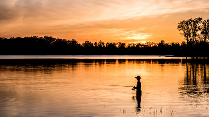 Two young kids are fishing under sunset of a lake