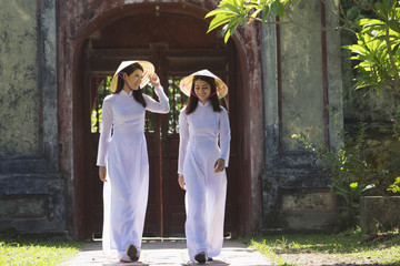 Vietnamese women wearing traditional suit walking in the temple
