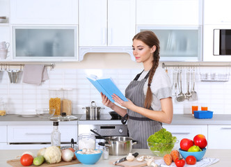 Young woman with cookbook at kitchen