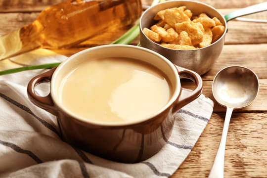 Delicious beer cheese soup with croutons on table