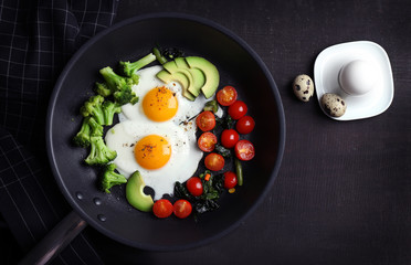 Pan with delicious roasted eggs and avocado on wooden background