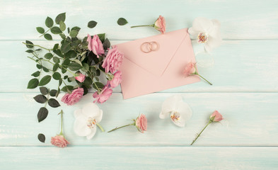 Pink roses, orchid and bridal rings with envelope for wedding invitations