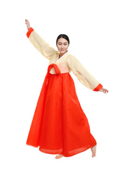 Beautiful young woman in Korean traditional costume dancing on white background