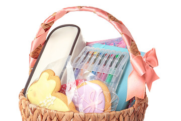 Easter basket with cookies and presents on white background