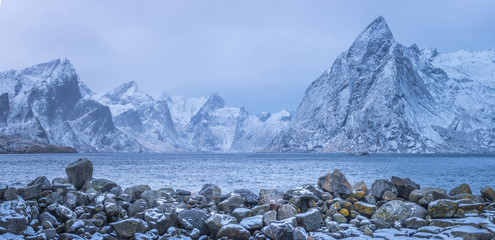 Winter mountains panorama view with stones at foreground