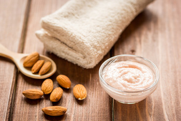 spa concept with almond nuts and scrub on wooden background