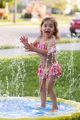 Child, girl or kid plays with water sprinkler toy outdoors during summer or spring to cool off in hot weather