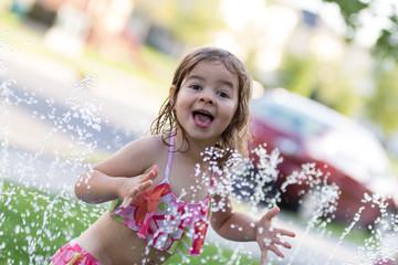 Cute little girl having fun outside with water sprinkler in summer garden