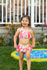 Summer outdoor water fun in the backyard. Little girl playing with water sprinkler toy.