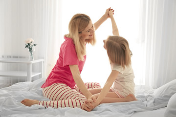 Happy mother and daughter sitting on bed at home