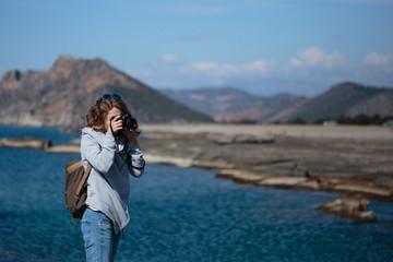 Young woman photographing rock ribbed Koru beach in Gazipasha Al