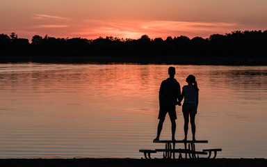 A man and a women are enjoying a passionate moment under sunset