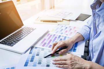 interior design or graphic designer renovation and technology concept - woman working with colour samples for selection.