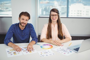 Portrait of smiling graphic designers sitting at desk