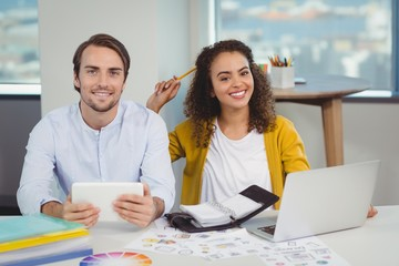 Portrait of smiling graphic designers sitting at table