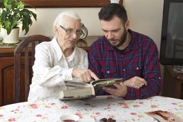 Babcia z wnuczkiem wspominają dawne czasy oglądając album ze zdjęciami.