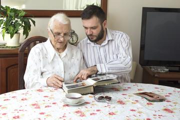 Babcia z wnuczkiem wspominają dawne czasy oglądając album ze zdjęciami. Wnuczek pokazuje babci album ze zdjęciami. Spotkanie rodzinne.