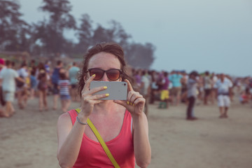 Young woman are taking photo on her mobile on Arambol beach at sunset in Goa, India