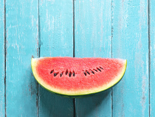 watermelon slice on ocean blue wood table summer time background concept.