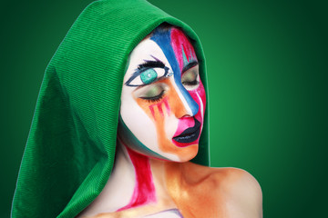 Creative make-up new conceptual idea. blue gold golden green red white bold body art painting. Crazy new graphic abstract picture on woman face surrealistic. professional photo. Creativity art lines