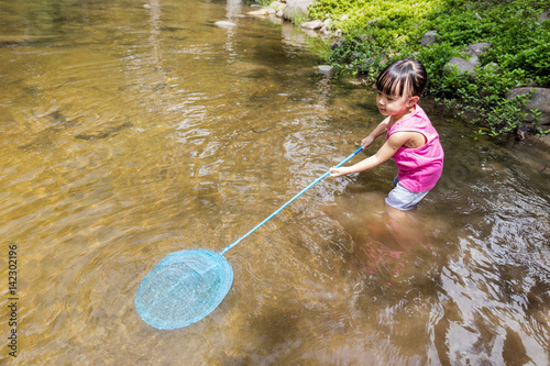 Asian chinese little girl catching fish with fishing net for Fish catching net