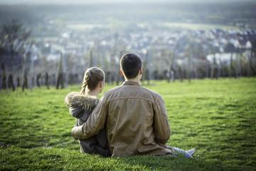 Junges Pärchen sitzt auf einer Wiese in den Weinbergen