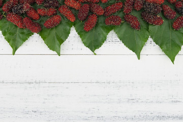Mulberries and leaves on white wood background with copy space from top view