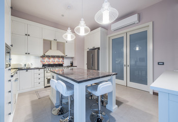 Kitchen Interior with Island, Sink, Cabinets,Tiled Floors in New Luxury Home