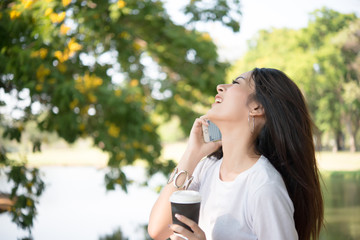 Young beautiful woman holding disposable coffee cup while talking on phone at nature outdoors Women lifestyle concept.