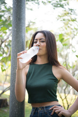 Young beautiful woman relaxing outdoors drinking water in the park.