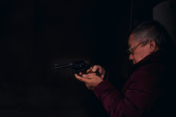 Dangerous old man pointing a gun at the target on dark background, selective focus on gun, dark tone,Crime concept