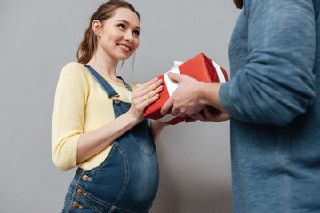 Young pregnant woman accepting present from her husband