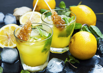 Fresh lemonade drinks glasses with mint leaves,lemons, ice cubes and sugar sticks