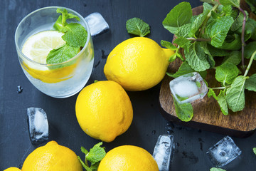 Lemon soda with mint leaves and ice cubes, fresh citrus infused water ingredients