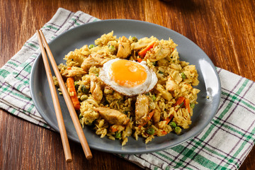 Fried rice nasi goreng with chicken egg and vegetables on a plate.