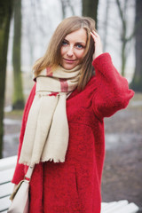 Beautiful girl in red coat with scarf posing. Portrait photography.