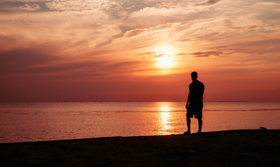 silhouette of man on the beach with sunset time