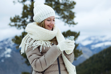 Beautiful young woman using her mobile phone over winter background.