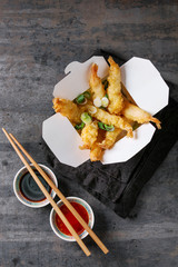 Fried tempura shrimps with rice and spring onion in paper to-go box. Served with sauces, chopsticks, textile napkin over old metal background. Top view, space. Asian take out dinner