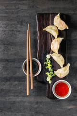 Gyozas potstickers on lettuce salad with sauces. Served in traditional china plate with chopsticks and spring onion on wood serving board over old metal background. Top view, space. Asian dinner