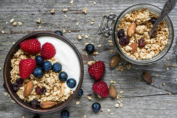 homemade granola with greek yogurt, nuts and fresh berries in a bowl